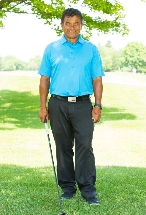 a photo of Lou Solarte.  Photo taken on a golf course.  He is smiling and posing with a golf club.